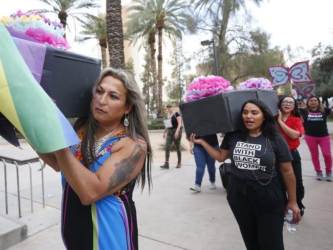 Karyna Jaramillo, 46, of Phoenix, carries an empty