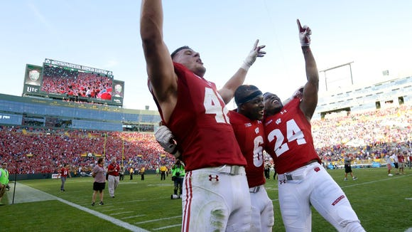 """Wisconsin linebacker T.J. Watt (left), running back Corey Clement (center) and safety Keelon Brookins sing along to """"Varsity"""" after the game."""