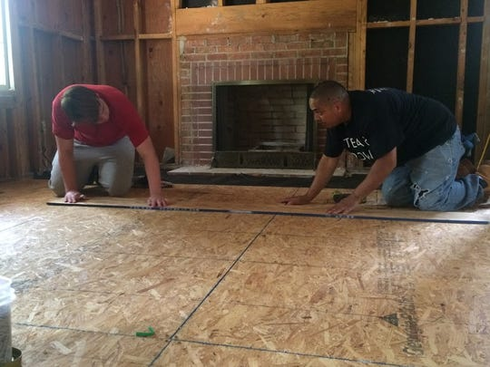 Clifton student Matthew Aymar, left, and Domingo Amante, a chaperone from Oakland, lay flooring on a home that was flooded during Hurricane Matthew in Lumberton, N.C. Aymar was among a group of 15 students who visited to help the community in July.