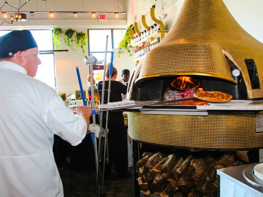 Pizzas are baked in wood-fired ovens in a centralized,