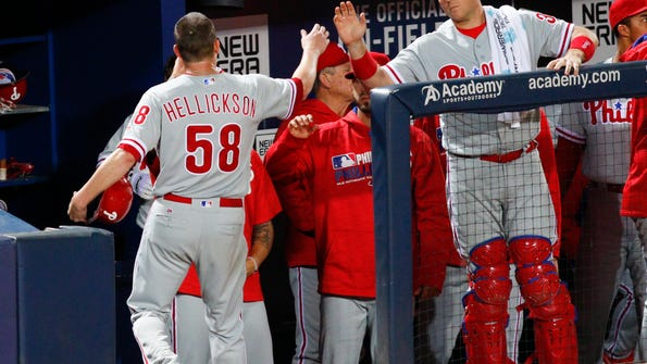 Philadelphia Phillies starting pitcher Jeremy Hellickson (58) is congratulated by catcher A.J. Ellis (34) after scoring a run during the third inning of a baseball game against the Atlanta Braves, Thursday, Sept. 29, 2016, in Atlanta. (AP Photo/Brett Davis)