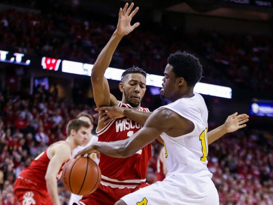 Michigan's Derrick Walton, right, drives against Wisconsin's Jordan Hill (11) during the first half of an NCAA college basketball game, Sunday, Feb. 28, 2016, in Madison, Wis. (AP Photo/Andy Manis)