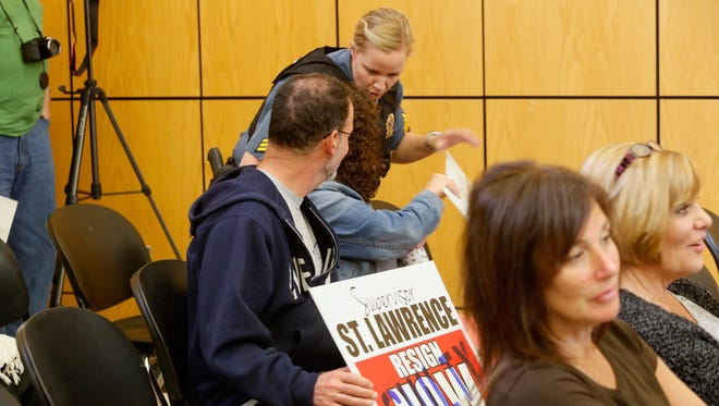 A Town of Ramapo police officer asks that protesters turn in their signs which would returned after the meeting.