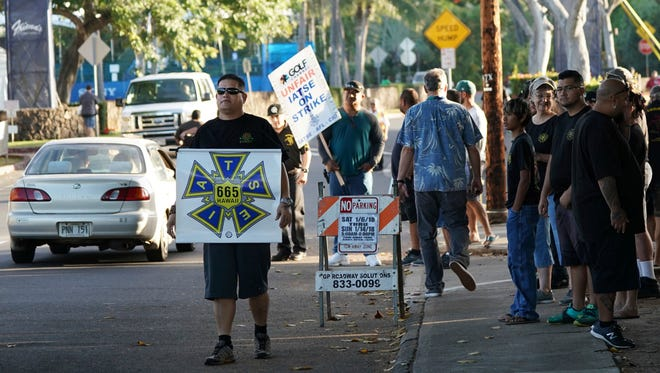 Members of the International Alliance of Theatrical Stage Employees strike outside the entrance to Sony Open golf tournament.