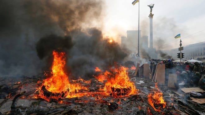 Tires burn as protesters attend an anti-government protest in downtown Kiev on Feb. 19.