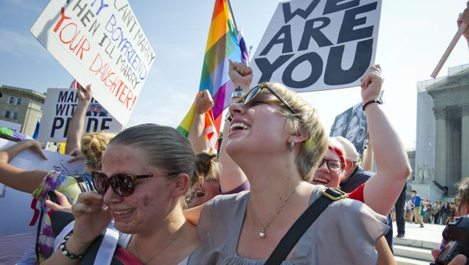 Gay rights activists react outside the U.S. Supreme Court in Washington D.C., on June 26, 2013, after the court struck down a controversial federal law defining marriage as a union between a man and a woman.