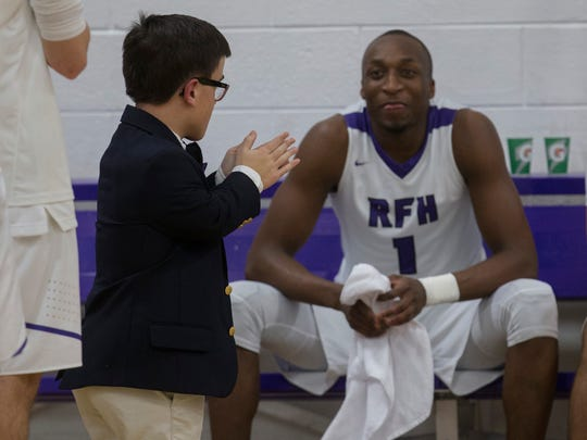 Rumson-Fair Haven boys basketball manager Jack Velcamp, who stands 4-foot-2, applauds during pregame introductions in front of Elijah McAllister.
