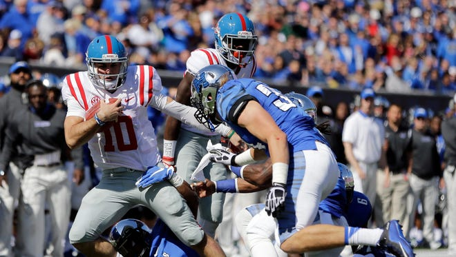 Mississippi quarterback Chad Kelly (10) is brought down by Memphis defenders in the first half.