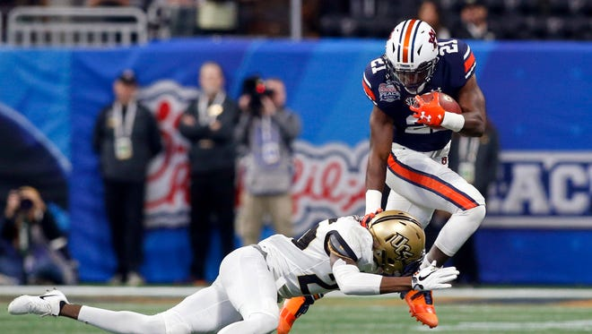 Auburn running back Kerryon Johnson is tackled by Central Florida's Kyle Gibson in the first quarter in the 2018 Peach Bowl at Mercedes-Benz Stadium on Jan. 1 in Atlanta.