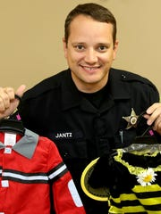 Salem Police Office Mark Jantz poses for a photo with costumes that have reflective material and bright colors.