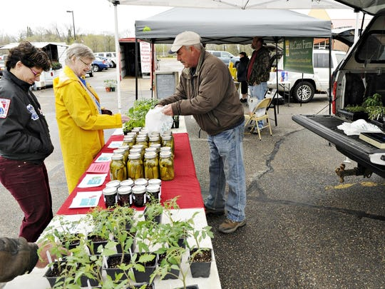 A vendor waits on customers during a past Sartell Farmers Market.