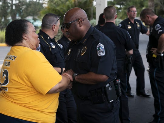Stephanie White, the mother of Stef'an Strawder is greeted by Fort Myers Police Chief Derrick Diggs before a candlelight vigil at location of the Club Blu shooting on Monday.