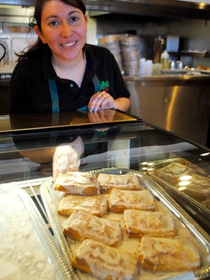 Cafe manager Michaela Scoll positions pastries inside a counter display case last week at International Delights cafe.
