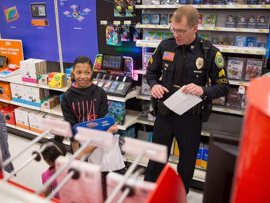 Muncie Police Officer Nate Sloan helps shop with Amaya
