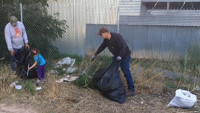 Volunteers use gloves and large garbage bags to pick up trash throughout Las Cruces.