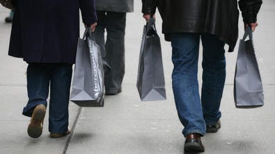 Shoppers walk along Fifth Ave. in New York. Americans spent slightly more in February but the gain still left consumer spending growing at a modest pace, held back by severe winter weather.