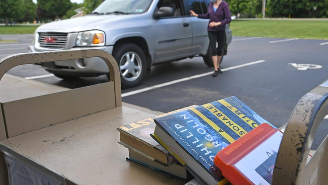 A book order waits on a cart on Monday at the Lincoln Community Center, 1255 Manchester Road, in Fairview Township. Lucy Angelo, background, of Millcreek Township, picked up the books for her husband, Richard.