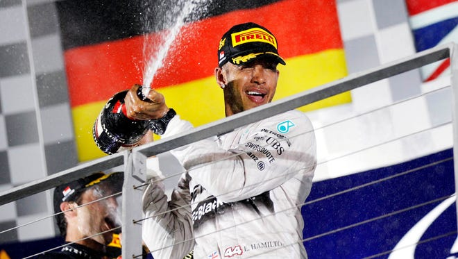 Mercedes Formula One driver Lewis Hamilton of Britain sprays champagne on the podium following the Singapore F1 Grand Prix at the Marina Bay street circuit in Singapore on Sept. 21, 2014.