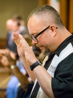 Pastor Mike Demastus of the Fort Des Moines Church of Christ prays as Deborah Maynard, a Wiccan from the Cedar Rapids area, delivers the opening prayer Thursday, April 9, 2015, in the Iowa House of Representatives at the Iowa Statehouse.