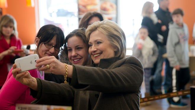 Democratic presidential candidate Hillary Clinton makes a selfie with customers, Sunday, Feb. 7, 2016, at a Dunkin' Donuts in Manchester, N.H.