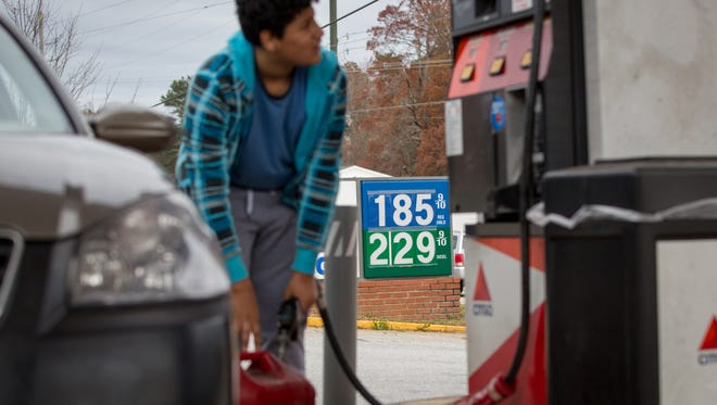 Cornelio Bonilla pumps gas at Best Food Mart gas station in Gainesville Ga. Sinking oil prices have cratered the stock market, but despite consumer savings on gas the U.S. economy has not seen a noticeable boost in overall consumption.