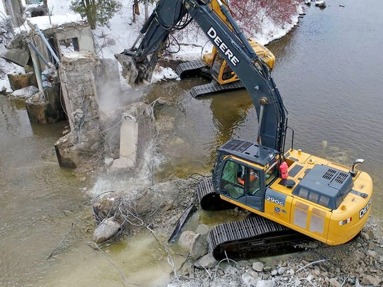 A large chunk of concrete crashes into the water as an excavator with a pulverizer (front) and an excavator with a hydraulic breaker, operated by workers with Terra Engineering and Construction of Madison, work to remove a portion of the dam. Work was being done to remove the final portions of the Estabrook Park dam on Milwaukee River on Tuesday.