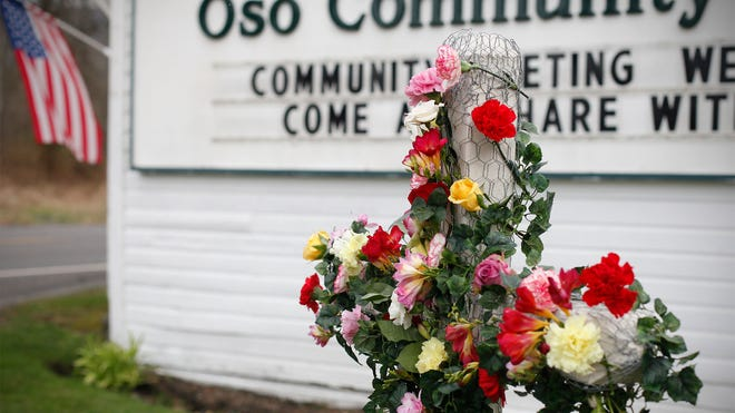 A cross is decorated with flowers in tribute to mudslide victims at the Oso Community Chapel on March 26 in Oso, Wash.