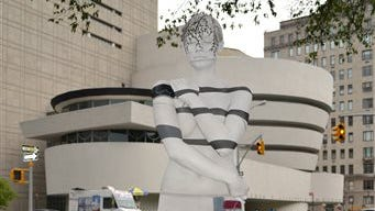 A model appears to blend into the background as she stands in front of the Guggenheim Museum in New York. Artist Trina Merry employs a meticulous process that relies on models to hold their pose perfectly still for hours as she paints their bodies so they blend into various New York City landmarks.
