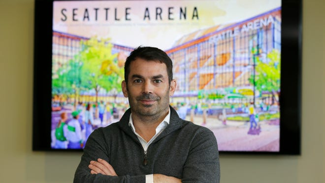 Chris Hansen, the investor hoping to build an arena to house a possible NBA or NHL franchise in Seattle's stadium district, poses Thursday in front of a drawing showing a potential arena design.