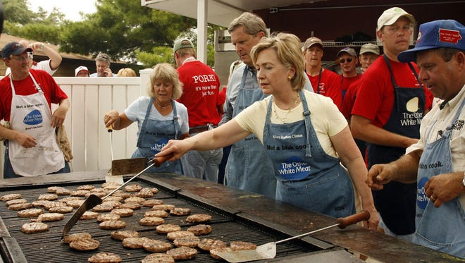 """Sen. Hillary Clinton flips pork patties at the Iowa Pork Producers tent on August 15, 2007 at the Iowa State Fair. Joining her are Christie and Tom Vilsack, left,  and Dana """"Spanky"""" Wanken, right."""