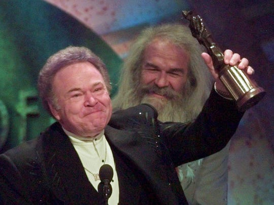 """In this April 23, 1997, file photo, musician Roy Clark celebrates after receiving the Pioneer Award at the Academy of Country Music Awards in Universal City, Calif. Clark, the guitar virtuoso and singer who headlined the cornpone TV show """"Hee Haw"""" for nearly a quarter century, died Nov. 15, 2018, due to complications from pneumonia at home in Tulsa, Okla., publicist Jeremy Westby said. He was 85."""