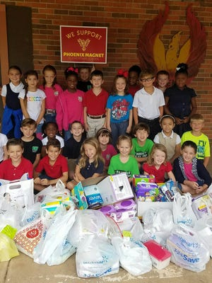 Second-graders at Phoenix Magnet Elementary School pictured with items collected for flood victims.