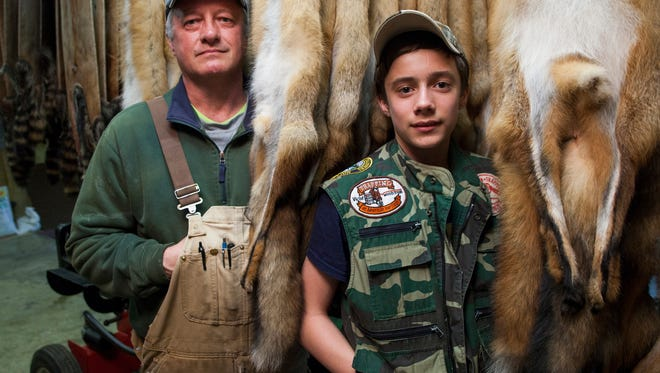 "Glenn Hanger stands with his son, Adam Hanger, in front of fox pelts that they trapped together near their home in Middlebrook. ""We do it because it's a part of how this country was founded, it's how I grew up,"" said Glenn Hanger, who's family settled in Middlebrook during the 1760s."