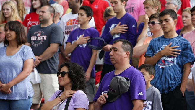 People in the crowd pay their respects with a moment of silence just before the National Anthem for West Layfetten High School student Christian Burns, who passed away on May 31, 2016 in a car accident at the IHSAA boys state track finale in Bloomington, IN on June 4, 2016 where he would have been competing.