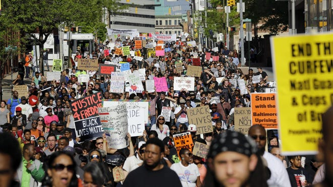 Protesters march through Baltimore the day after charges were announced against the police officers involved in Freddie Gray's death.