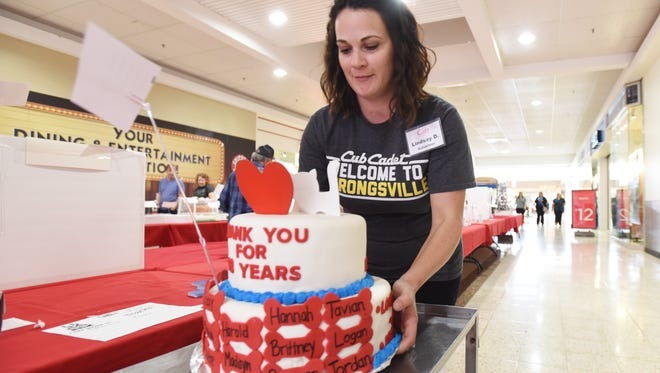 Volunteer Lindsay Dodson of American Pride collects a cake during the Carr Center Cake Auction at the Colony Square Mall on Friday.
