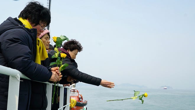 In this photo provided by South Korean Ministry of Oceans and Fisheries, a relative of missing passengers of the sunken Sewol ferry throws a flower during religious services in waters off Jindo, South Korea, Tuesday, March 28, 2017.
