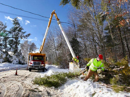 Brian Murray of Lucas Tree Experts hauls away giant tree branches cut by Don Libby as they clean up limbs and debris causing downed wires along Wood Road Friday, Dec. 30, 2016 in Gorham, Maine. Nearby residents are without power as a result of the heavy wet snow that fell overnight.