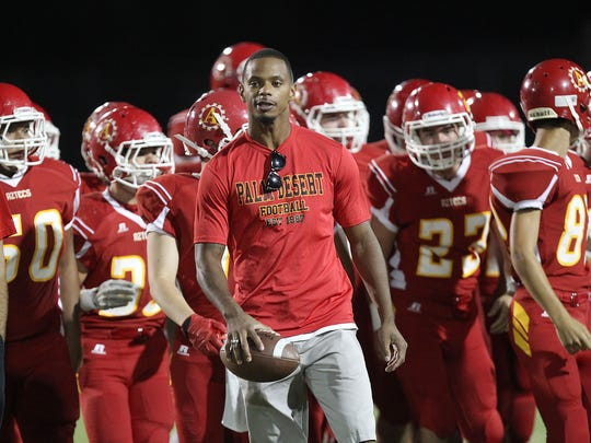 Palm Desert's James Dockery leads the Aztecs onto the field against La Quinta High on Sept. 26, 2014.