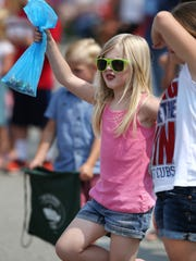 Aurora Schreiber, 5, Merrillville, dances to the music from a passing marching band in the The CarmelFest Fourth of July parade on South Rangeline Road on Saturday, July 4, 2015.