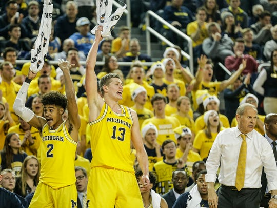 Michigan's Jordan Poole (2) and Moe Wagner cheer for teammates during the second half against UCLA on Dec. 9, 2017.