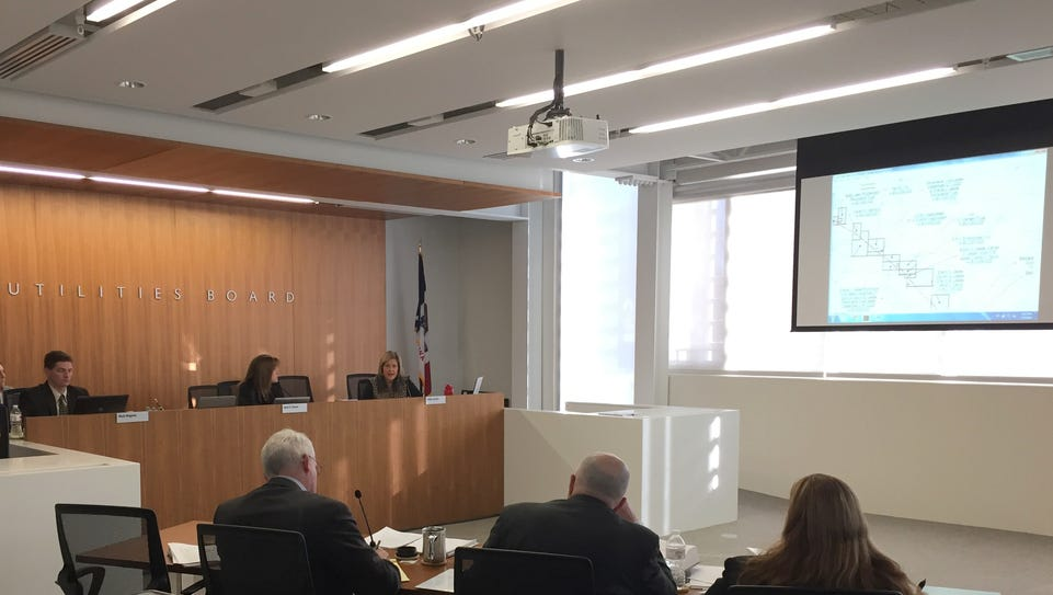 The three-member Iowa Utilities Board, in back, consults