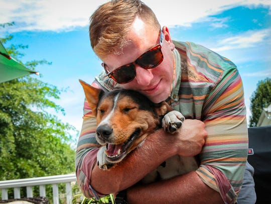 Pfc. Austin Highcock hugs his beloved dog, Scout McCoy.