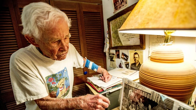 John Tripp, a veteran of World War II who served in the famed 10th Mountain Division, looks over some memorabilia from his years in the military in his home in Carbondale, Colo. (Anna Stonehouse/The Aspen Times via AP)