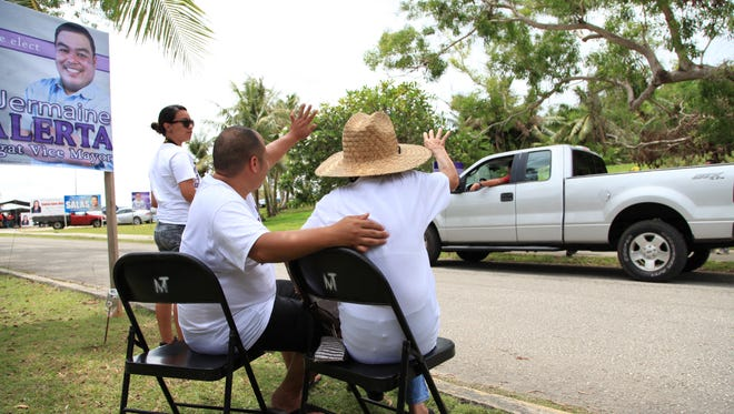 This file photo shows campaign supporters at the entrance to Oceanview Middle School greeting passing vehicles during the election for the Agat Vice Mayor on Saturday, June 6, 2015.