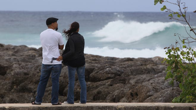 In this file photo, waves crash near the breakwater at the boat basin in Hagåtña.