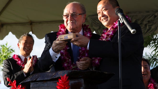 In this December 2011 file photo, FIFA President Joseph S. Blatter, left, and Guam Football Association President Richard Lai, show off the FIFA block during the Inauguration of the Football Turf and Mini Pitches of the Guam Football Association. Federal prosecutors said Lai accepted $400,000 in bribes that year from international soccer officials.
