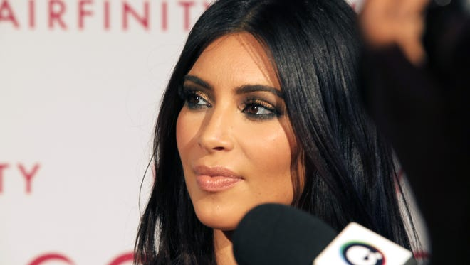 Kim Kardashian talks to the media on her arrival at the Hairfinity party in central London, Saturday, Nov. 8, 2014.