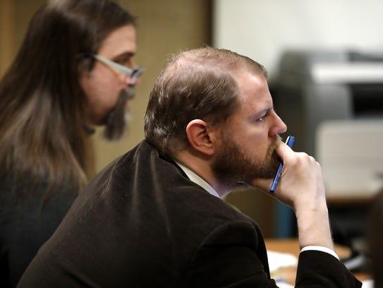 Public defender Ben Szilagyi, right, listens Friday