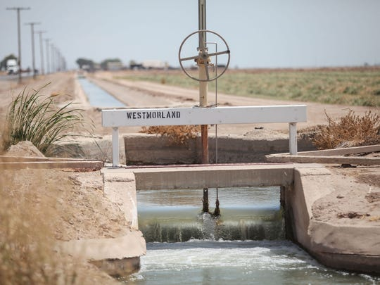 An Imperial Irrigation District canal carries irrigation water past farmland near Westmorland, in California's Imperial Valley, on July 18, 2017.